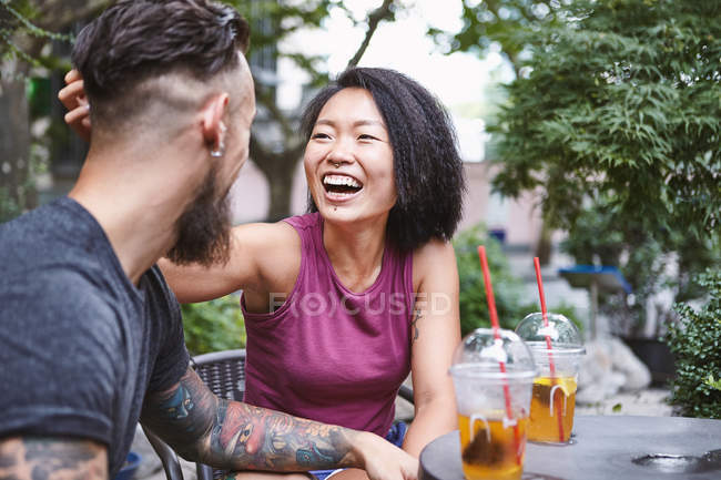 Multi ethnic hipster couple laughing at sidewalk cafe, Shanghai French Concession, Shanghai, China — Stock Photo