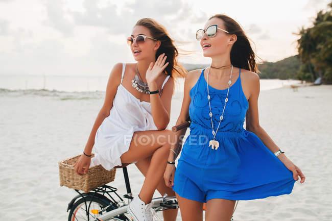 Duas jovens mulheres em sundresses com bicicleta na praia de areia, Krabi, Tailândia — Fotografia de Stock