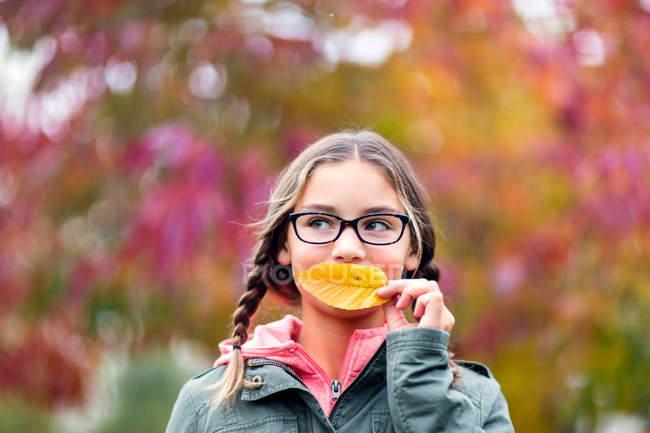 Ritratto di ragazza con trecce e occhiali che copre la bocca con il foglio che osserva via — Foto stock