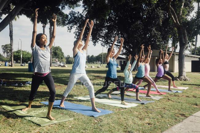 Школьницы практикуют йогу в одной позе на школьной спортивной площадке — стоковое фото