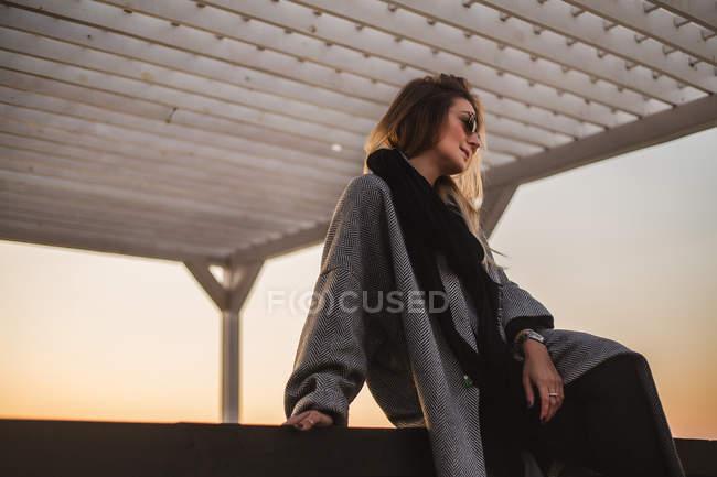 Портрет жінки носять зимове пальто і сонцезахисні окуляри, хтось дивитися вбік — стокове фото