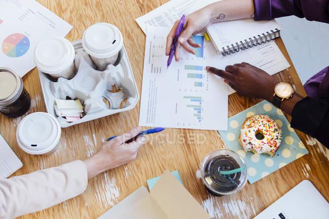 Обрезанный вид сверху на руки бизнесвумен и кофейные чашки на столе — стоковое фото