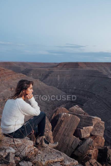 Jovem mulher sentada nas rochas e olhando a vista, chapéu mexicano, Utah, EUA — Fotografia de Stock