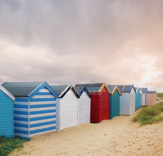 Row of colourful beach huts and storm clouds, Southwold, Suffolk, England — Stock Photo