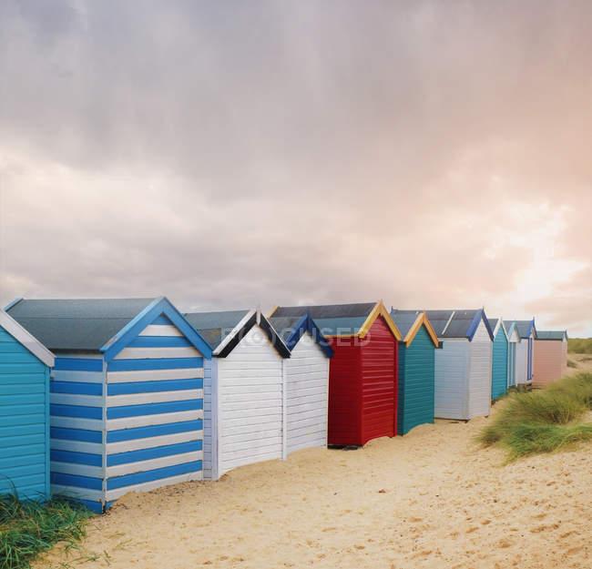Рядок барвистий пляж хатин і грозових хмар, Southwold, Саффолк, Англія — стокове фото