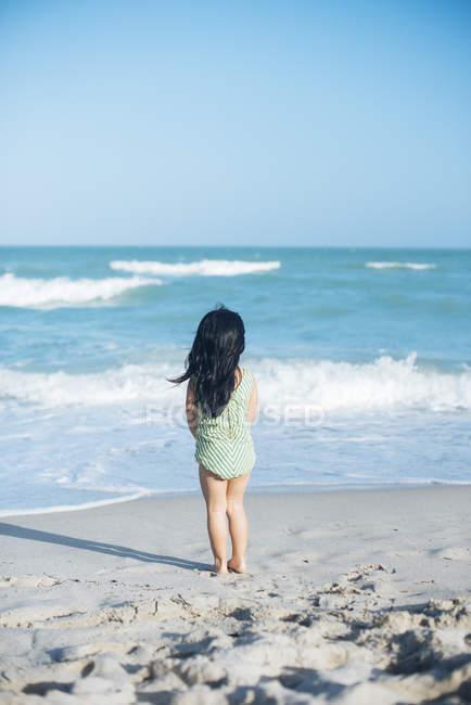Заднього вигляду мало дівчина стояла на пляжі — стокове фото