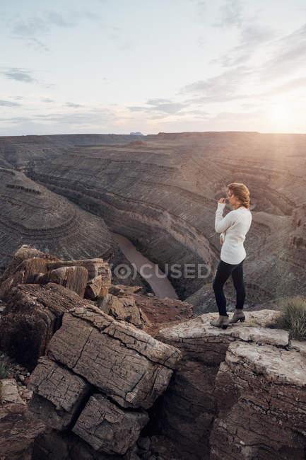 Jovem de pé em rochas e olhando a vista, chapéu mexicano, Utah, EUA — Fotografia de Stock