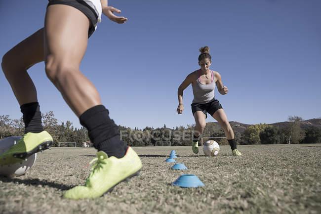 Deux jeunes femmes dribble de ballons de football — Photo de stock