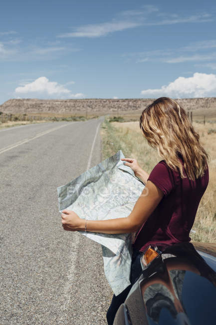 Mulher, encostado no carro olhando o mapa na estrada — Fotografia de Stock