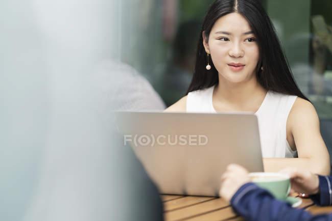Kollegen treffen im Café und Laptop verwenden — Stockfoto