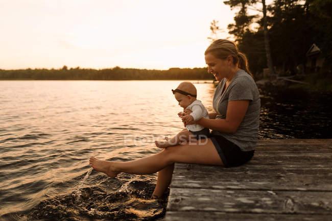 Матері, сидячи на пристані з немовляти дочки, хлюпалися ноги в озеро — стокове фото