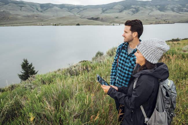 Пара стояли біля Діллон водосховище, використовуючи цифровий планшет, Silverthorne, Колорадо, США — стокове фото