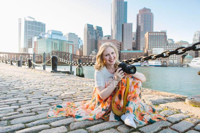 Jovem fotógrafo feminino sentado na calçada cais, Boston, Massachusetts, EUA — Fotografia de Stock