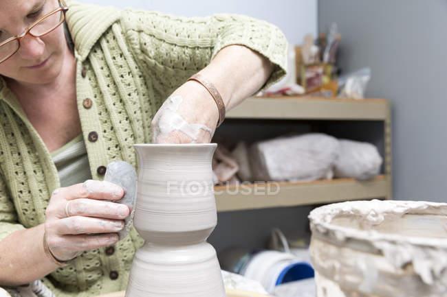 Femme travaillant avec céramique dans l'atelier d'artiste — Photo de stock