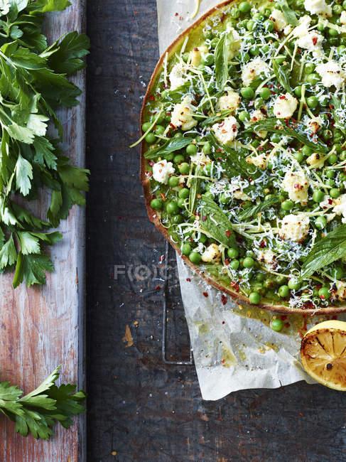 Erhöhten Blick auf frische grüne Erbsen und Salat Blatt pizza — Stockfoto