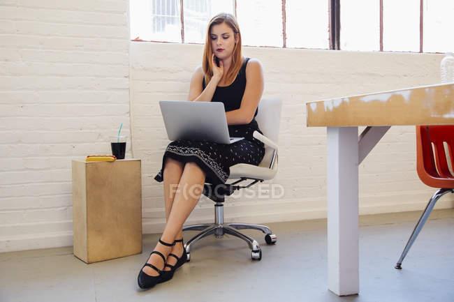 Donna d'affari caucasica in sedia ufficio utilizzando il computer portatile — Foto stock