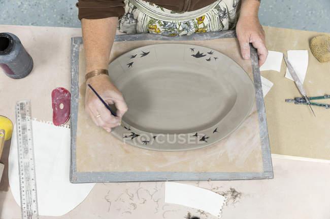 Femme peinture sur plateau en céramique — Photo de stock