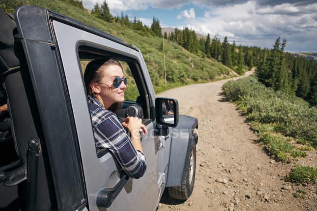 Junge Frau auf Roadtrip von Autofenster im Felsengebirge, Breckenridge, Colorado, Usa — Stockfoto