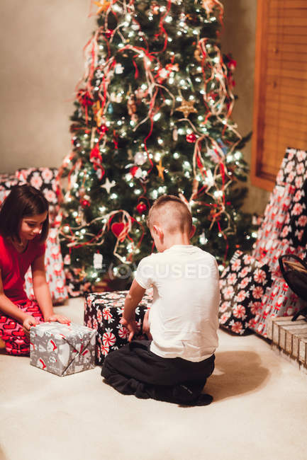 Brother and sister unwrapping gifts on Christmas day — Stock Photo