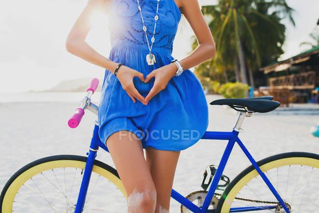Jeune femme à vélo en forme de coeur avec les mains sur la plage de sable fin, Krabi, Thaïlande — Photo de stock