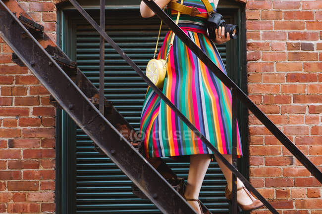Young woman on industrial building stairway with digital camera — Stock Photo