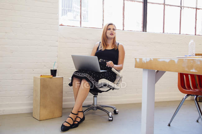 Кавказька бізнес-жінка в офісному кріслі за допомогою ноутбука — стокове фото