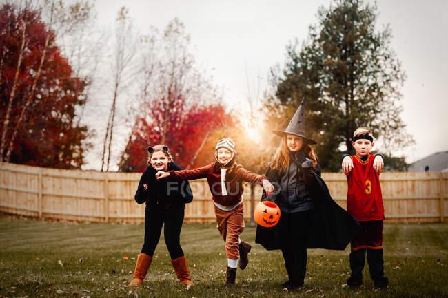 Portrait de garçons et de filles en costumes d'Halloween dans le jardin au coucher du soleil — Photo de stock