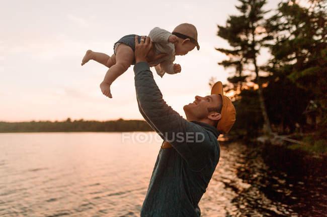 Чоловік тримає вгору baby дочка на березі озера — стокове фото