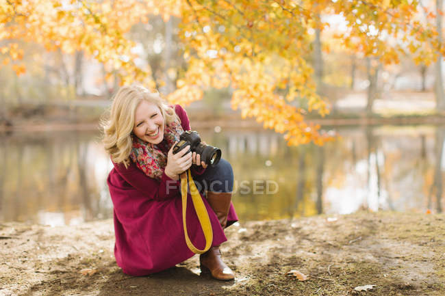 Young woman crouching to take photo in autumn park — Stock Photo