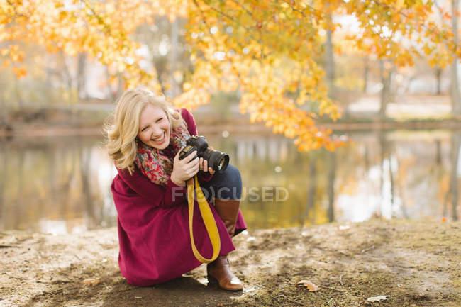 Mulher jovem, agachando-se para tirar a foto num parque outono — Fotografia de Stock