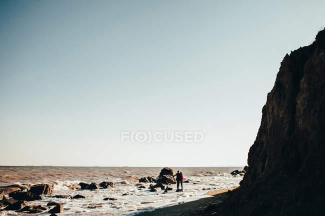 Далеких подання середині дорослих пара стоячи на скелі в елегантній на пляжі, Одеська область, Україна — стокове фото