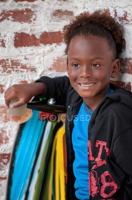 Портрет молодий хлопчик на вулиці проведення скейтборд — стокове фото