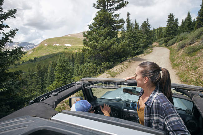 Young woman looking out from four wheel convertible in Rocky mountains, Breckenridge, Colorado, USA — Stock Photo