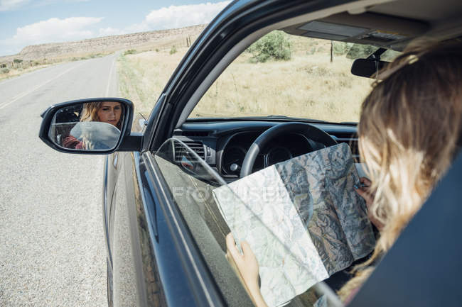 View over shoulder of woman sitting in car with map — Stock Photo