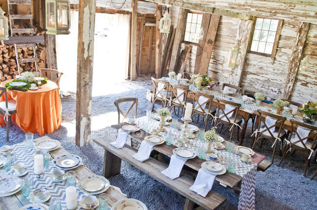 Place settings with table decorations in barn — Stock Photo