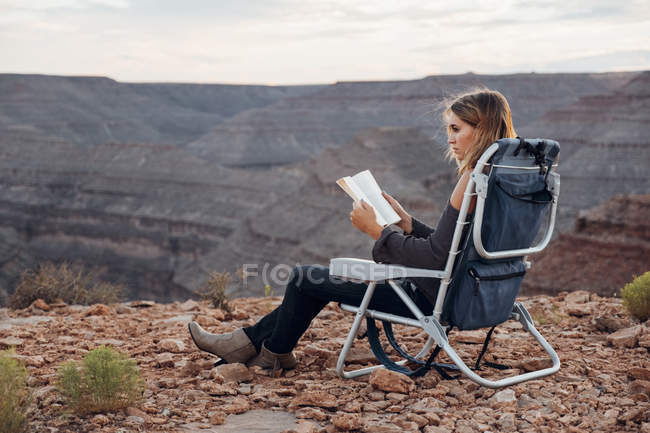Young woman sitting on camping chair and reading book, Mexican Hat, Utah, USA — Stock Photo