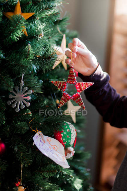 Gros plan de l'enfant en mettant en place les décorations de Noël — Photo de stock