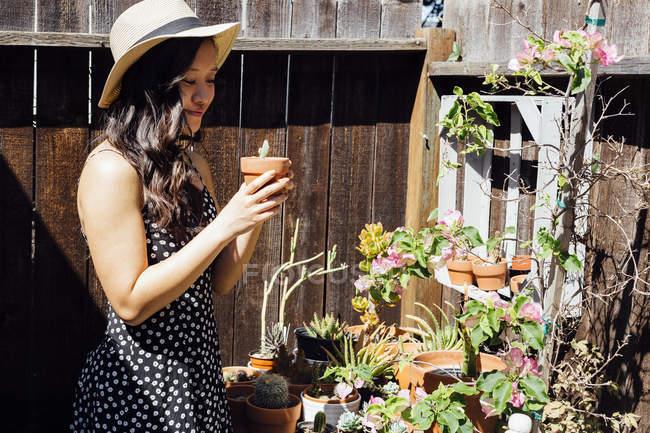 Молоду жінку на вулиці, намагаючись горщиках рослини в саду — стокове фото