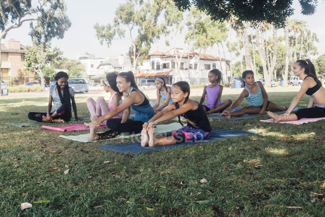 Школьницы практикуют йогу касаясь пальцев на школьном спортивном поле — стоковое фото