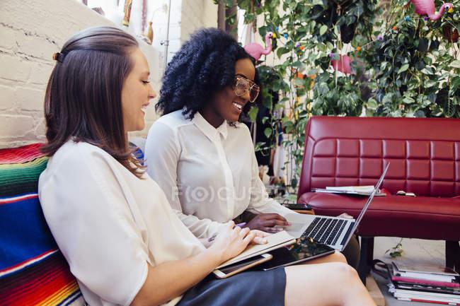 Colleghi seduti insieme sul divano in ufficio utilizzando il computer portatile — Foto stock