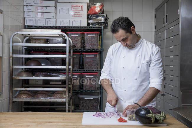 Chef in der Großküche schneidet rote Zwiebeln — Stockfoto