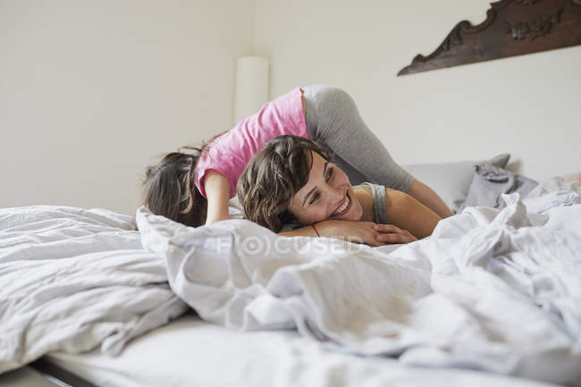 Mother and daughter playing on bed in light bedroom — Stock Photo