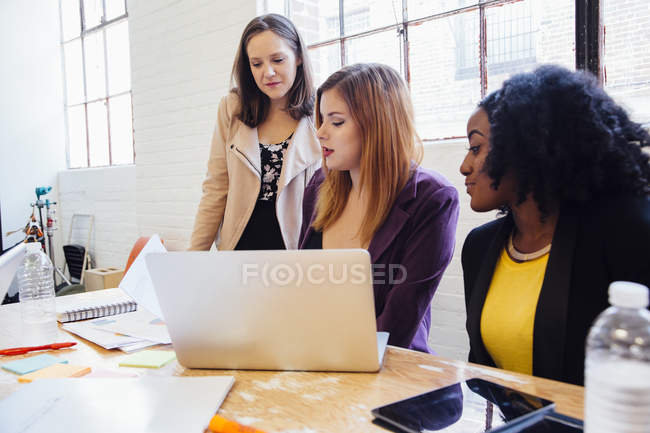 Three colleagues in modern office looking at paperwork — Stock Photo