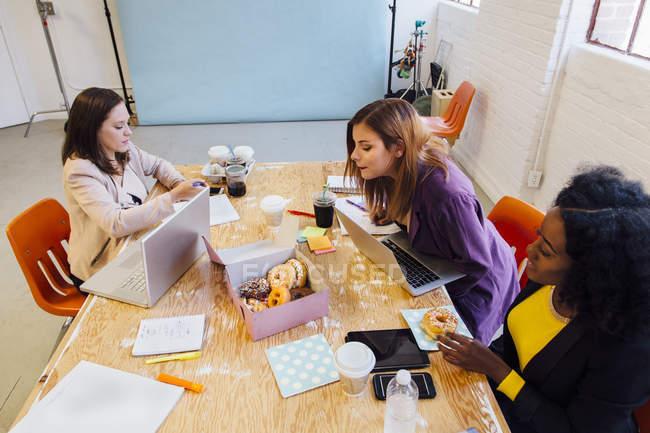 Collègues qui travaillent ensemble au bureau partage beignes — Photo de stock