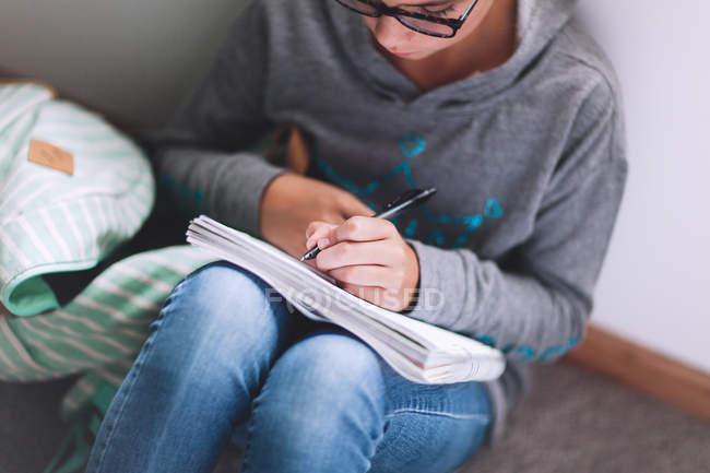 Fille assise au sol et rédaction de devoirs — Photo de stock