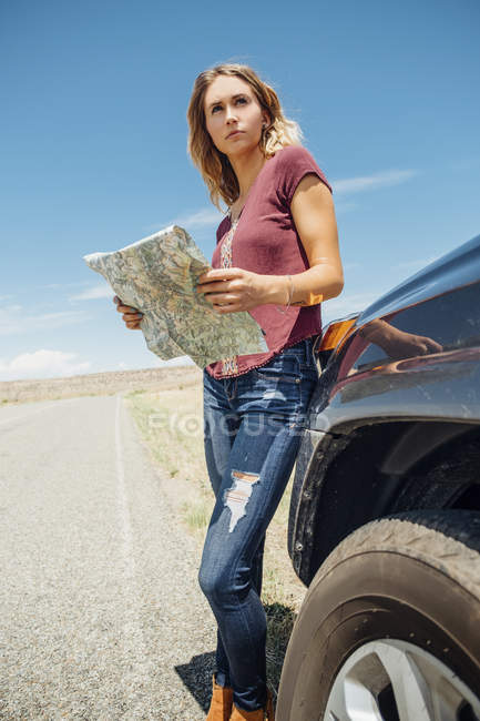 Mulher com mapa por carro olhando para longe — Fotografia de Stock