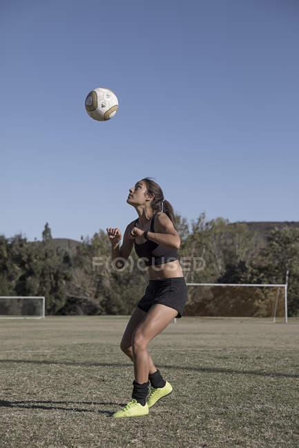 Junge Frau auf Fußballplatz mit Fußball — Stockfoto
