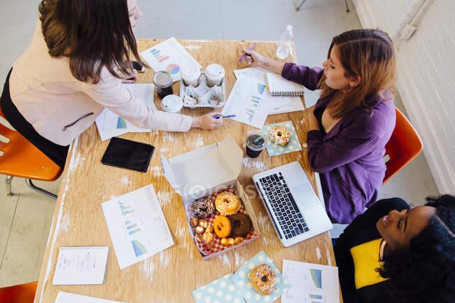 Vista ad alto angolo di colleghi femminili che lavorano insieme e mangiano ciambelle — Foto stock