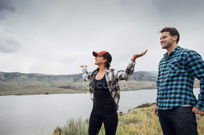 Пара ходьба поблизу Діллон водосховище, молода жінка зброї підняли, Silverthorne, Колорадо, США — стокове фото