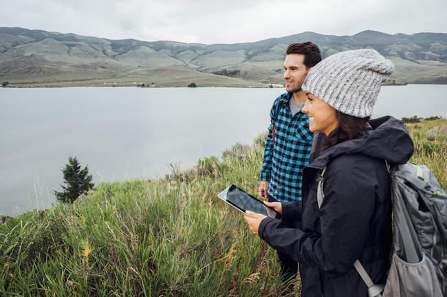 Пара походи, стоячи біля Діллон водосховище, молоді жінки, що тримає цифровий планшет, Silverthorne, Колорадо, США — стокове фото